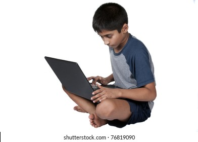 An handsome Indian kid having fun with laptop