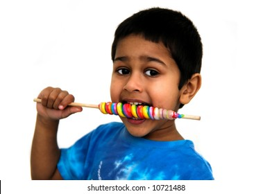 An handsome Indian kid savoring his colorful candy