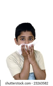 An handsome Indian kid wiping his face due to an allergy