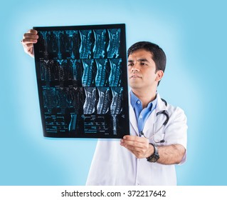 Handsome Indian Male Doctor examining MRI scan or Xray, standing isolated over blue background