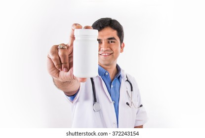 Handsome Indian Male Doctor holding empty white or blank Pills bottle. standing isolated over white background