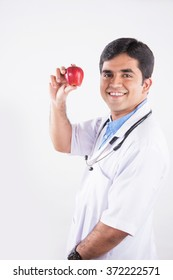 Handsome Indian Male Doctor showing or eating fresh red apple. standing isolated over blue background