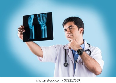 Handsome Indian Male Doctor studying MRI scan or Xray, standing isolated over blue background