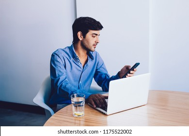 Handsome indian man in formal wear talking via mobile phone connected to 4g internet sitting at desktop, business male graphic designer sending text message via smartphone working at company