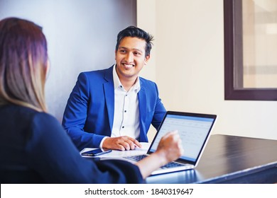 Handsome Indian man giving KYC interview to a woman with laptop in a bank or office