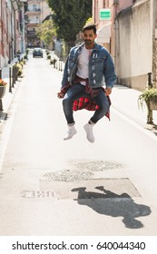 Handsome Indian man jumping in an urban context. Street fashion and style.
