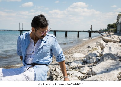 Handsome Indian man posing in a vacation context. Street fashion and style.