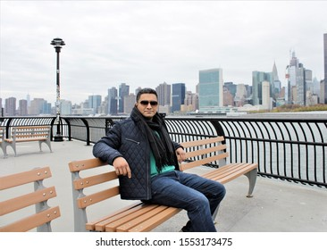 A handsome Indian man sitting on a bench on a waterfront in front of Manhattan Skyline.