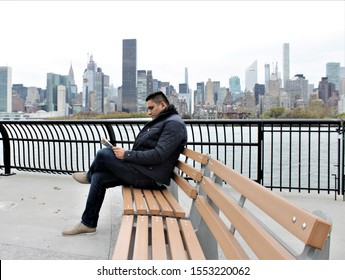 A handsome Indian man sitting on a bench and reading a magazine on a waterfront in front of Manhattan Skyline.