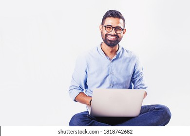 Handsome Indian man sitting and working on laptop over studio white background