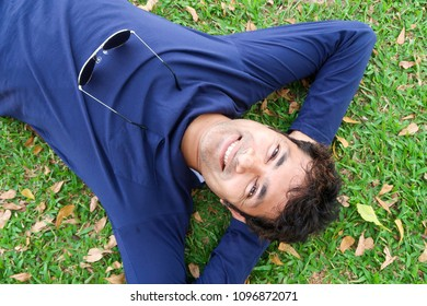 Handsome indian man smiling relax on nature green grass at park / feel good and happy man