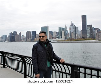 A handsome Indian man standing on a waterfront in front of Manhattan Skyline.