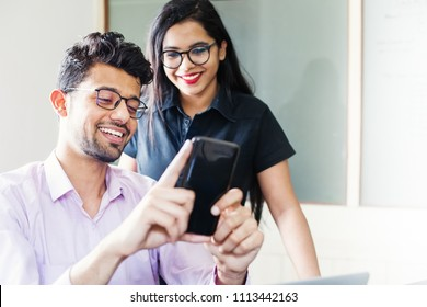 Handsome indian man using his phone and showing it to beautiful indian young woman
