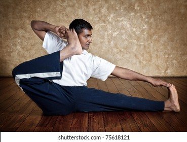 Handsome Indian man in white shirt doing akarna dhanurasana, archer pose indoors on wooden floor at grunge background