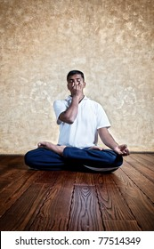 Handsome Indian man in white shirt doing nadi suddhi pranayama in padmasana position with Vishnu mudra gesture indoors on wooden floor at grunge background. Space for text