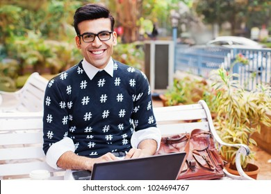 Handsome Indian man working as a freelancer on his laptop outside