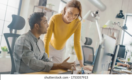 Handsome Indian Professional Sitting at His Desk Working on Laptop Computer, Young Beautiful Team Leader Gives Advice about Project Details. Office with Young Professionals Work. Dutch Angle.