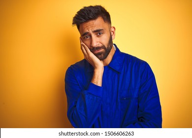 Handsome indian worker man wearing uniform over isolated yellow background thinking looking tired and bored with depression problems with crossed arms.