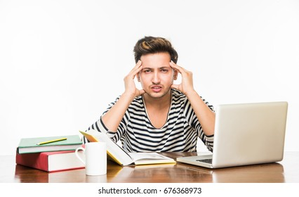 Handsome Indian/Asian college student studying on laptop computer while pile of books kept over table with coffee Mug, Over plain white background