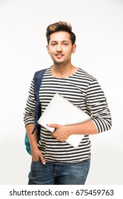 Handsome Indian/Asian Male college student standing with Laptop Computer, against white background, isolated
