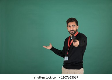 Handsome interviewer wearing his ID and holding a mic giving it to the guest, Standing on a green background.
