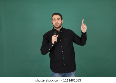 Handsome interviewer wearing his ID and holding the mic and pointing his finger at something up, Standing on a green background.