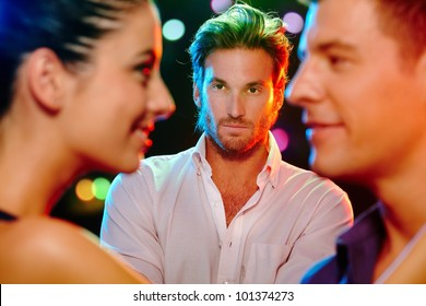 Handsome jealous man looking at flirting couple on dance floor.