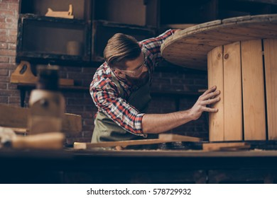 handsome joiner check wood.  Stylish young entrepreneur with beautyful hairstyle and saved glasses work at his workstation. he love his job and workplace.