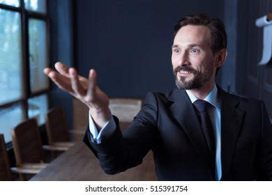 Handsome joyful man looking at his hand