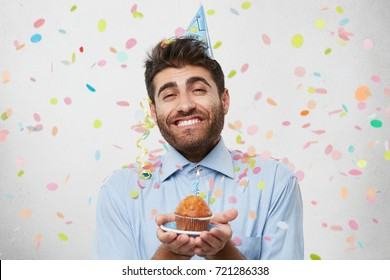 Handsome joyful young man with thick beard wearing shirt and holiday cap holding hands in front of him, offering you to have a piece of his birthday cake. People, celebration, festive event and party