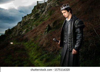 Handsome king with sword stands in contemplation with hill and parts of castle in the background