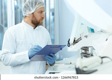 Handsome laboratory assistant in white cap and blue gloves doing experiments. Attractive doctor with red beard in lab coat checking new modern equipment. Young medical worker writing results.