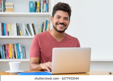 Handsome latin american man with beard working at computer at home