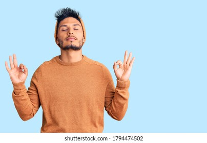Handsome latin american young man wearing winter sweater and wool hat relax and smiling with eyes closed doing meditation gesture with fingers. yoga concept.
