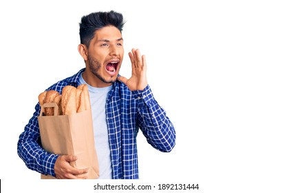 Handsome latin american young man holding paper bag with bread shouting and screaming loud to side with hand on mouth. communication concept.