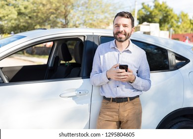 Handsome Latin man smiling while holding mobile phone near brand new car