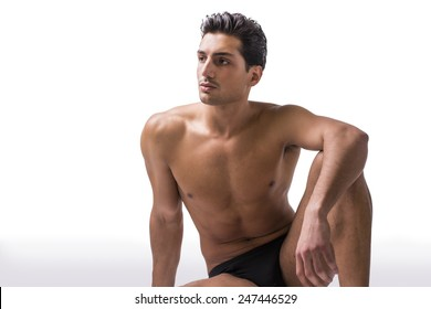 Handsome latin young man sitting naked on floor, wearing only underwear. Muscular build