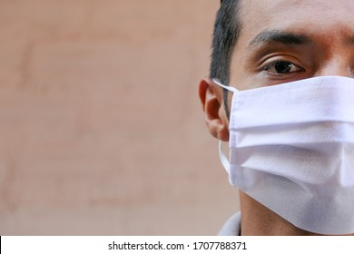 Handsome Latino young man with a medical mask. Close-up of a 35-year-old man wearing a face mask to protect himself against infection with the influenza virus or coronavirus.