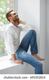 Handsome laughing man relaxing on window sill. Fun concept