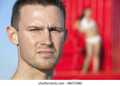 Handsome lifeguard on beach with bikini clad woman watching from tower