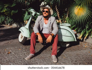 handsome in a light jacket, hat and red trousers, sunglasses with mustache and beard about posing retro scooter, fashionable clothes, brutal man, stylish outfit, Tiffany, walk down the street
