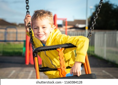 A handsome little boy with ADHD, Autism, Aspergers Syndrome plays happily on a swing in the summer sun