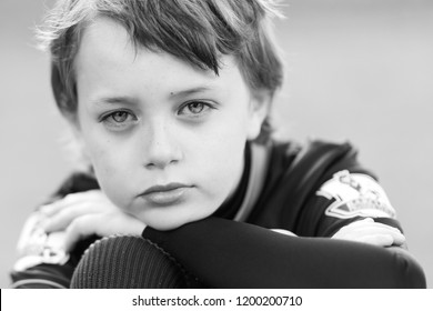 A handsome little boy with ADHD, Autism, Aspergers Syndrome looking into the camera, feeling alone and slightly sad