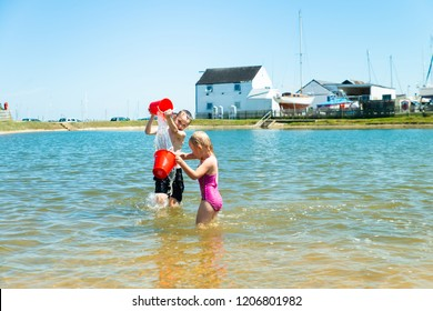 A handsome little boy with ADHD, Autism, Asperger Syndrome playing with his sister throwing buckets of water over each other by the sea on a beautiful summers day, energetic