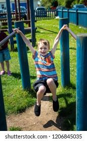 A handsome little boy with ADHD, Autism, Asperger Syndrome plays at the park on the monkey bars, parallel bars smiling and having fun, energetic