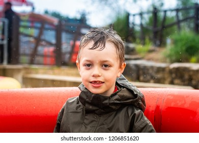 A handsome little boy with ADHD, Autism, Asperger Syndrome enjoys a day out at a theme park on a water ride smiling and having fun