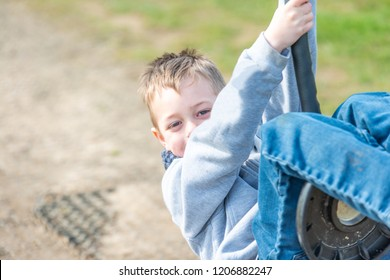A handsome little boy with ADHD, Autism, Asperger Syndrome plays at the park smiling and having fun, energetic