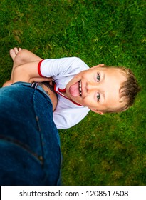 A handsome little boy with ADHD, Autism, Aspergers Syndrome hangs on to his fathers leg being playful and full of energy, smiling and happy