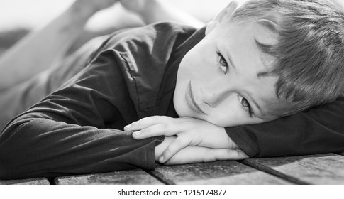 A handsome little boy with ADHD, Autism, Aspergers syndrome stares and smiles into the camera, handsome little boy