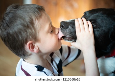 A handsome little boy with ADHD, Autism, Aspergers Syndrome cuddles and plays with his loyal loving pet dog, adorable